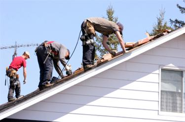 Roof Installation in Moyock NC. Three roofers laying new shingle on a roof in Moyock.